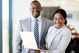 Two smiling business people holding a laptop