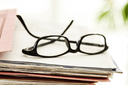 Spectacles on a stack of papers